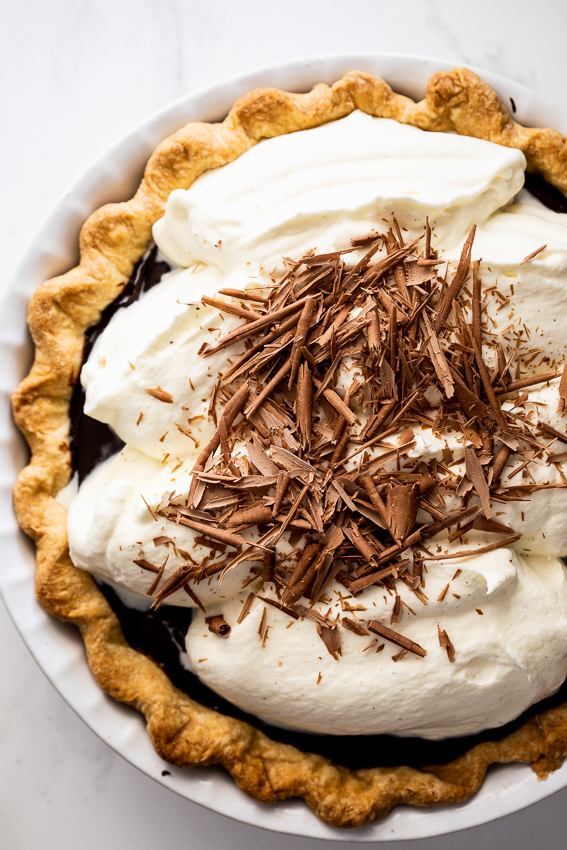 Chocolate cream pie with whipped cream and chocolate shavings.