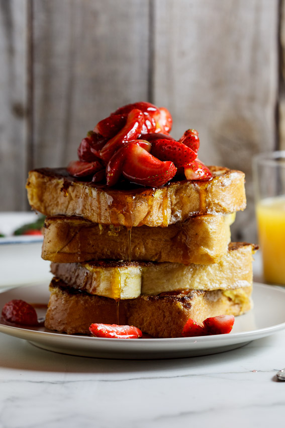 Stack of Lemon French toast with strawberries and maple syrup.