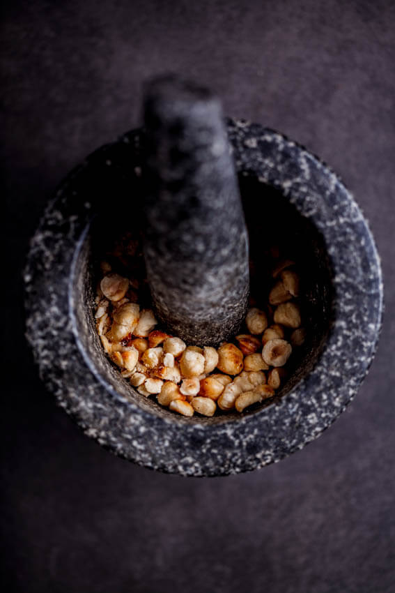 Roasted hazelnuts in pestle and mortar
