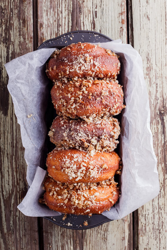 Soft, fluffy yeasted doughnuts covered in caramel glaze and dunked in crunchy cinnamon-flavored nuts.