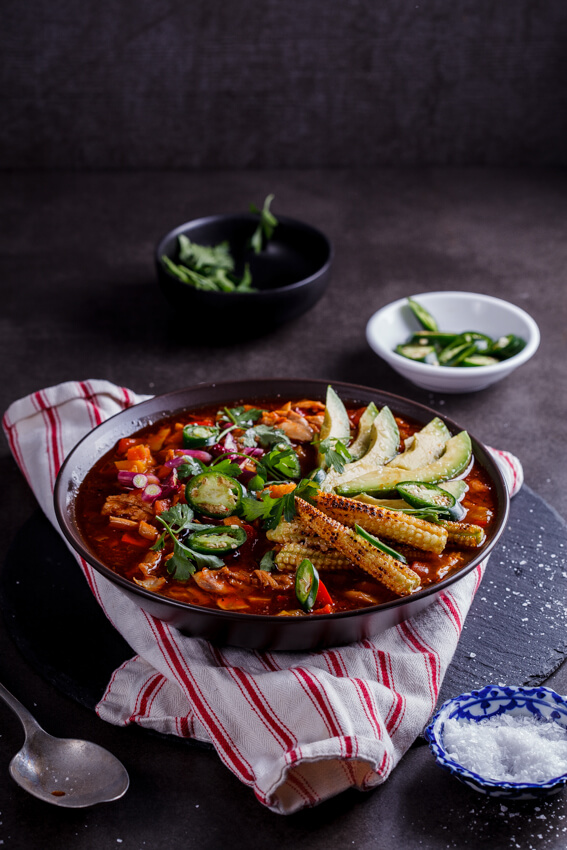 Aromatic Mexican chicken soup with sweet, charred baby corn makes for a showstopping meal when served with fresh jalapeños and avocado.