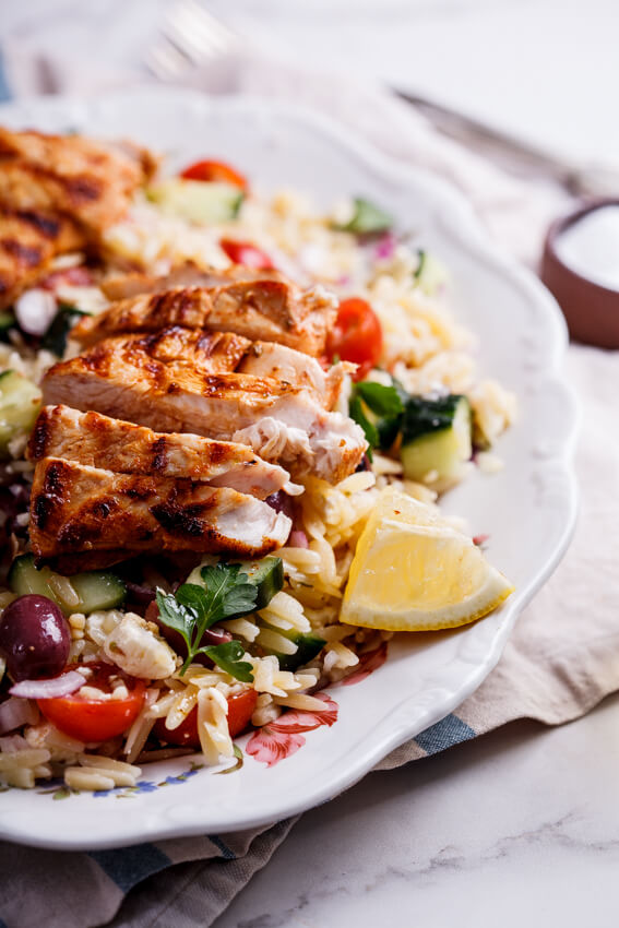 This Greek orzo salad topped with succulent grilled chicken is a fantastic recipe for an easy lunch or light dinner and makes an excellent packed lunch.