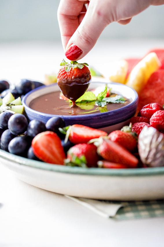 Dipping strawberry into vegan chocolate ganache