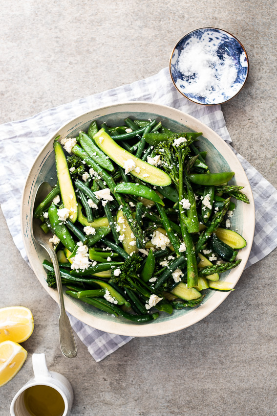 Easy steamed spring vegetables with feta cheese in blue and white bowl