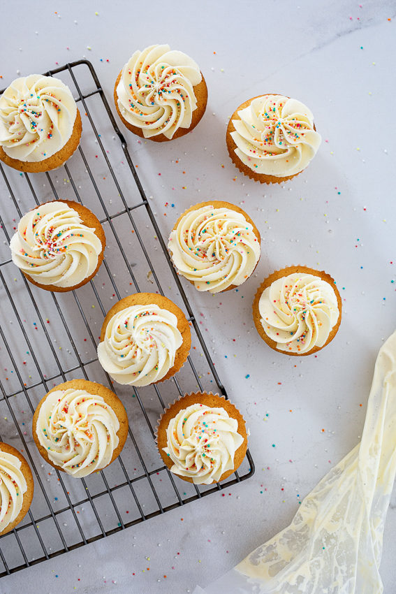 Vanilla cupcakes topped with swirls of whipped buttercream.