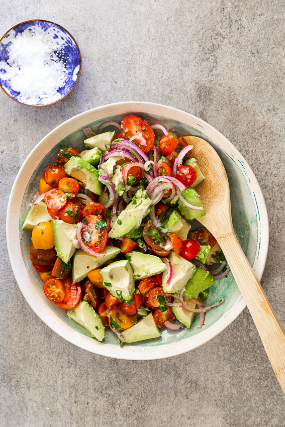Tomato avocado salad in serving bowl with wooden spoon.