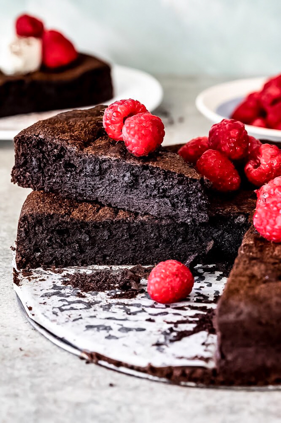 Flourless chocolate cake topped with fresh raspberries.