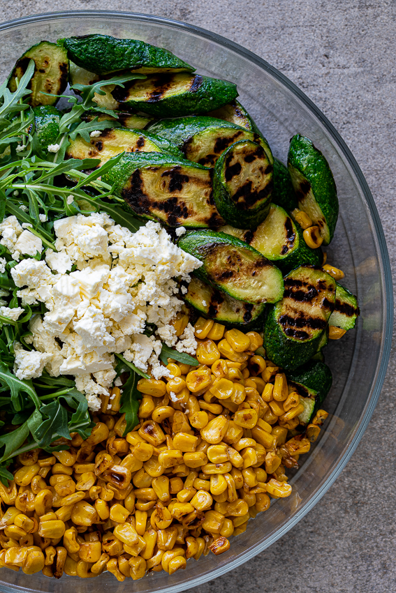 Grilled zucchini, corn and feta in bowl.