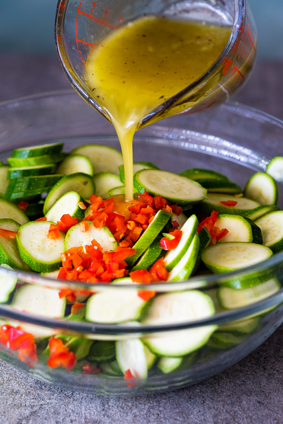 Lemon olive oil marinade poured onto zucchini salad