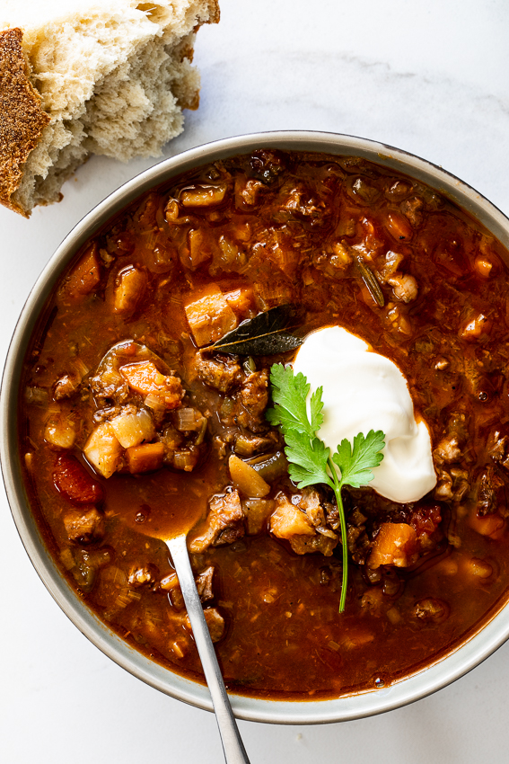 Vegetable beef soup served with sour cream.