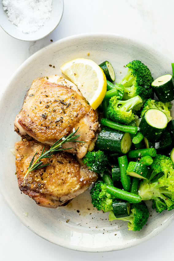 Rosemary lemon chicken thighs served with vegetables.