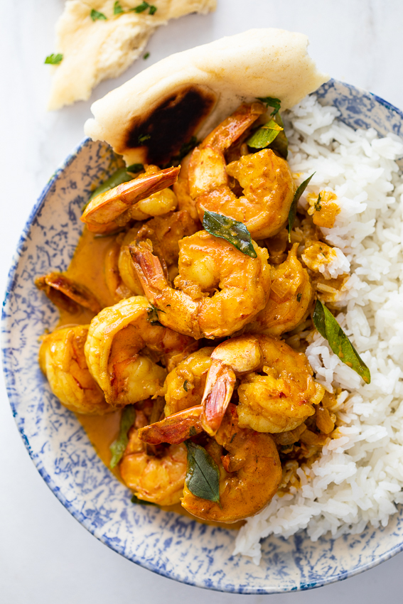 Creamy shrimp curry with rice and naan bread.