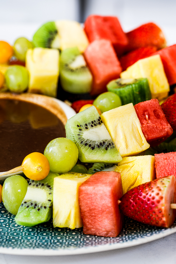 Fresh fruit skewers with chocolate sauce.