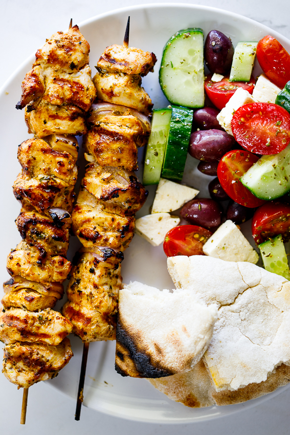Greek grilled chicken skewers with salad and pita.