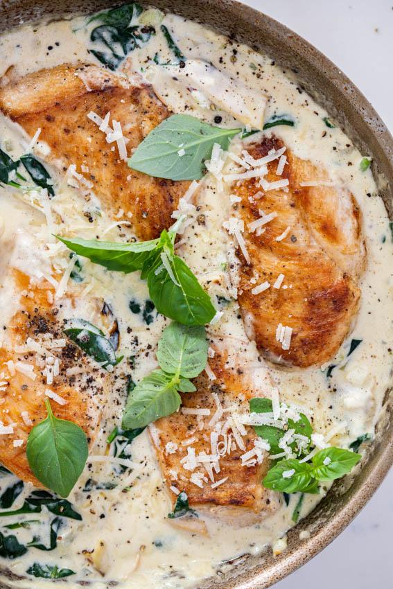 Juicy pan-seared chicken breasts in creamy spinach artichoke sauce.