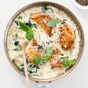 Juicy pan-seared chicken breasts in creamy spinach artichoke sauce.