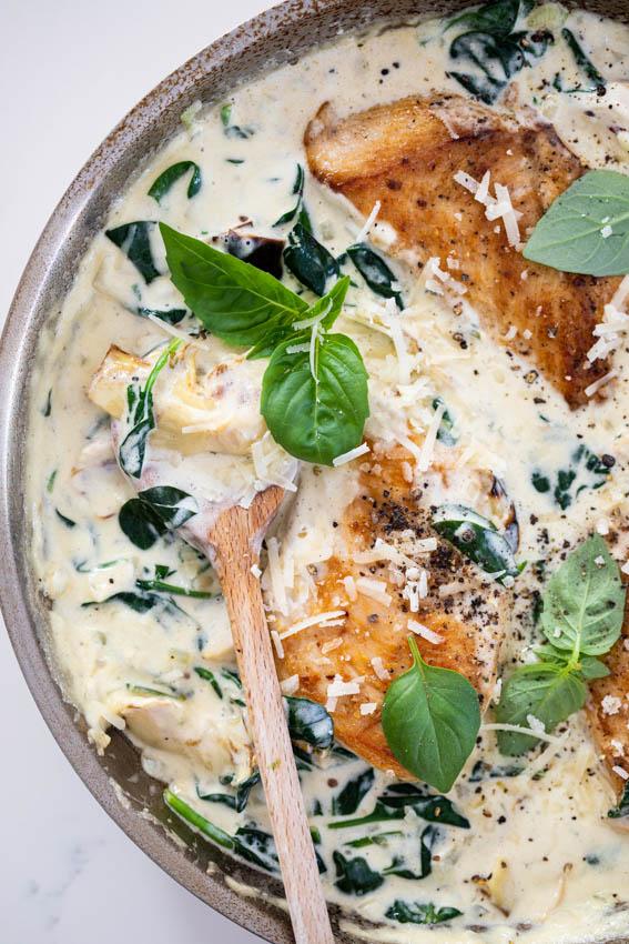 Creamy spinach artichoke chicken with fresh basil.