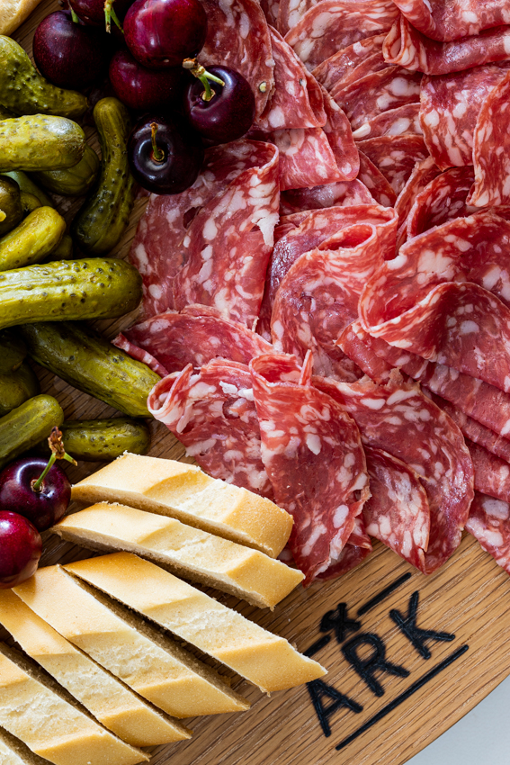 Salami, pickles and bread on a charcuterie board.