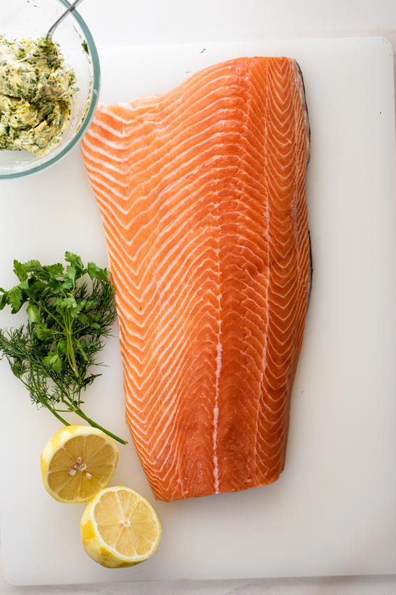 Side of salmon rubbed with garlic herb butter before being baked.