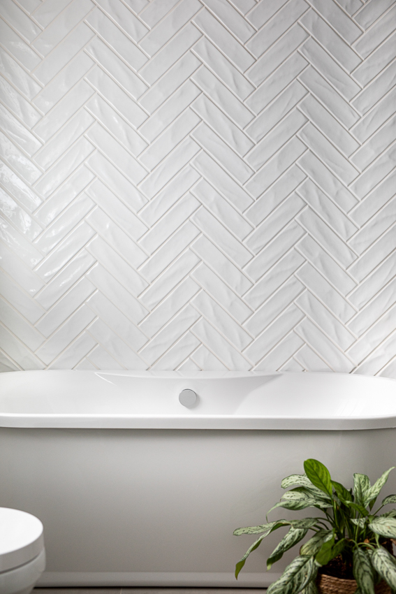 White herringbone tiles behind white freestanding bathtub.