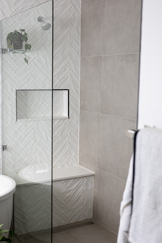 Large walk in shower with white herringbone and grey tiles