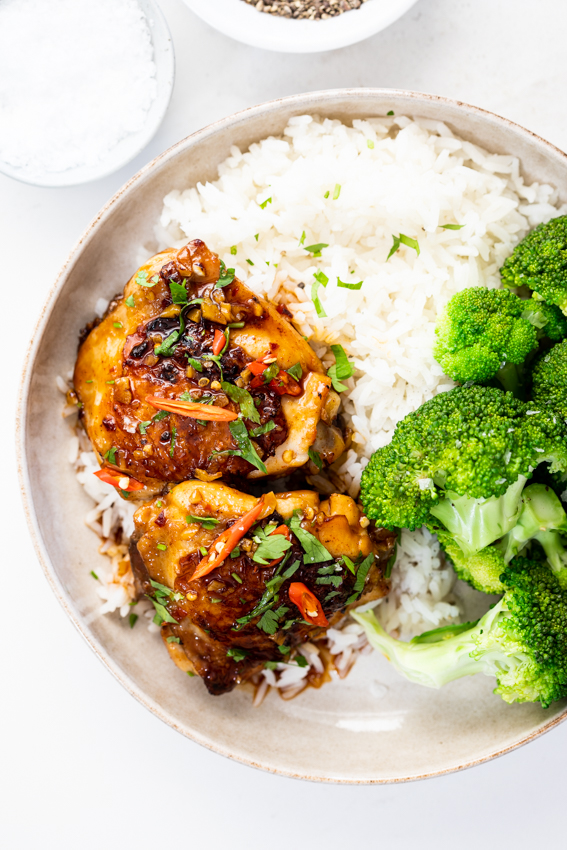 Sweet and spicy baked chicken thighs with rice and broccoli.