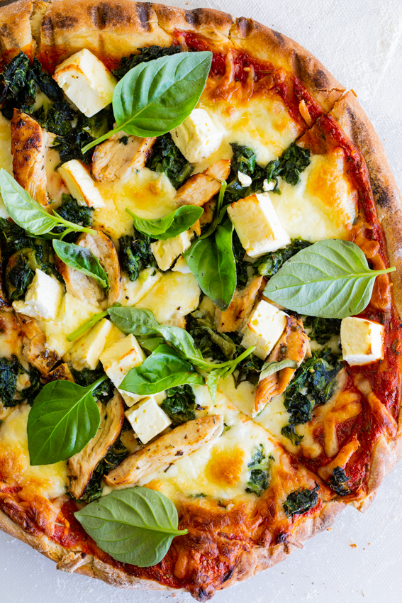 Grilled Greek chicken pizza with feta and spinach.